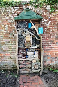 an insect hotel standing upright next to a garden wall