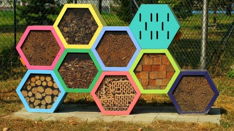 a painted bug hotel with multiple sections