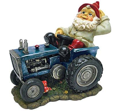 a large garden gnome driving a blue tractor